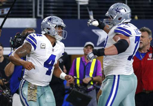 Dallas Cowboys' Dak Prescott (4) and Zack Martin (70) celebrate a touchdown scored by Prescott on a running play in the first half of an NFL football game against the Kansas City Chiefs on Sunday, Nov. 5, 2017, in Arlington, Texas.