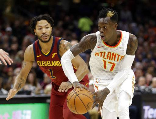 Atlanta Hawks' Dennis Schroder (17), from Germany, looks to pass against Cleveland Cavaliers' Derrick Rose (1) in the first half of an NBA basketball game, Sunday, Nov. 5, 2017, in Cleveland.