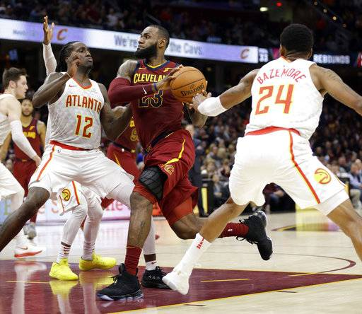 Cleveland Cavaliers' LeBron James (23) drives against Atlanta Hawks' Taurean Prince (12) and Kent Bazemore (24) in the second half of an NBA basketball game, Sunday, Nov. 5, 2017, in Cleveland.