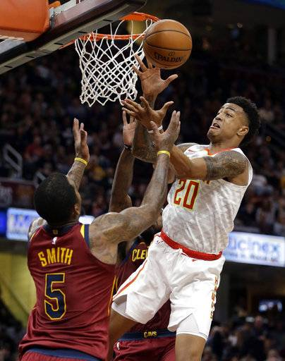 Atlanta Hawks' John Collins (20) and Cleveland Cavaliers' JR Smith (5) battle for a rebound in the first half of an NBA basketball game, Sunday, Nov. 5, 2017, in Cleveland.