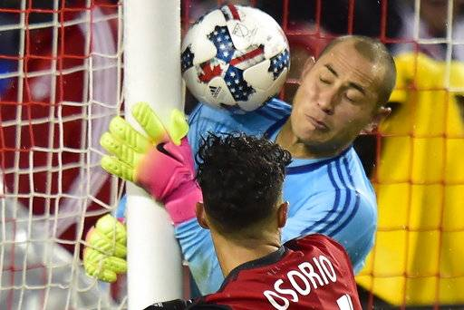 New York Red Bulls goalkeeper Luis Robles, top, fails to stop the ball from going past him during second-half MLS soccer game action against Toronto FC in Toronto, Sunday, Nov. 5, 2017. The ball was called a no-goal by the referee after the play. (Frank Gunn/The Canadian Press via AP)