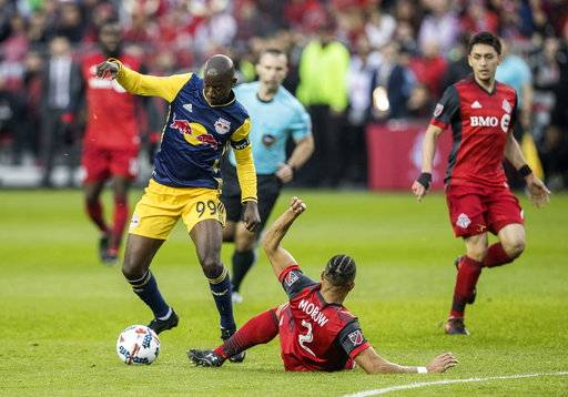 Toronto FC defender Justin Morrow (2) goes down as New York Red Bulls forward Bradley Wright-Phillips (99) gains control of the ball during first-half MLS soccer game action in Toronto, Sunday, Nov. 5, 2017. (Mark Blinch/The Canadian Press via AP)