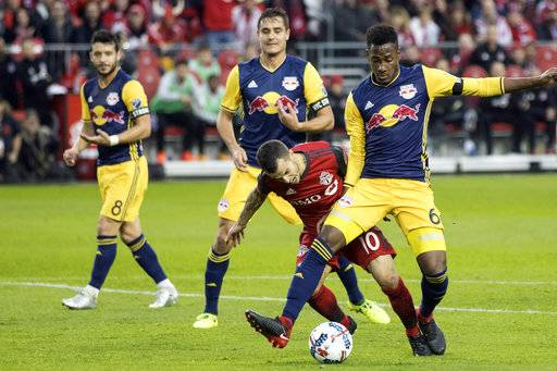 Toronto FC forward Sebastian Giovinco (10) goes down as he is brushed by New York Red Bulls defender Michael Murillo (62) during first-half MLS soccer game action in Toronto, Sunday, Nov. 5, 2017. (Chris Young/The Canadian Press via AP)