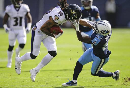 Tennessee Titans cornerback Brice McCain (23) grabs Baltimore Ravens wide receiver Chris Moore (10) by the face mask in the first half of an NFL football game Sunday, Nov. 5, 2017, in Nashville, Tenn.