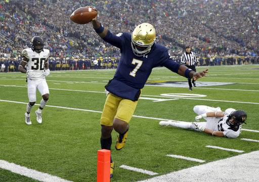 Notre Dame quarterback Brandon Wimbush scores a touchdown during the first half of an NCAA college football game against Wake Forest, Saturday, Nov. 4, 2017, in South Bend, Ind.