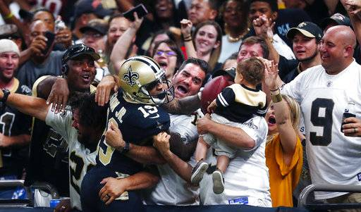 New Orleans Saints wide receiver Ted Ginn (19) leaps into the stands and hands the ball to a child after scoring on a touchdown reception in the second half of an NFL football game against the Tampa Bay Buccaneers in New Orleans, Sunday, Nov. 5, 2017.