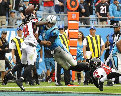 Carolina Panthers' Cam Newton (1) dives over the goal line for a touchdown against Atlanta Falcons' Desmond Trufant (21) and Deion Jones (45) in the first half of an NFL football game in Charlotte, N.C., Sunday, Nov. 5, 2017.