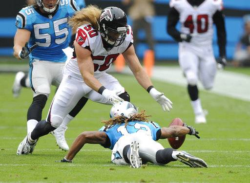 Carolina Panthers' Kaelin Clay (12) tries to recover his fumble as Atlanta Falcons' Brooks Reed (50) closes in during the first half of an NFL football game in Charlotte, N.C., Sunday, Nov. 5, 2017. The Panthers recovered the ball.