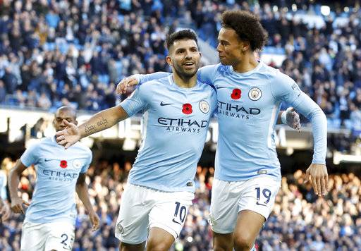 Manchester City's Sergio Aguero, left, celebrates scoring his side's second goal of the game during the English Premier League soccer match between Manchester City and Arsenal, at the Etihad Stadium, in Manchester, Sunday, Nov. 5, 2017. (Martin Rickett/PA via AP)