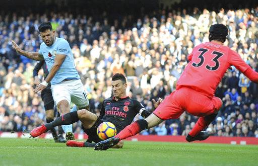 Manchester City's Sergio Aguero, left, shoots the ball during the English Premier League soccer match between Manchester City and Arsenal at Etihad stadium, Manchester, England, Sunday, Nov. 5, 2017.