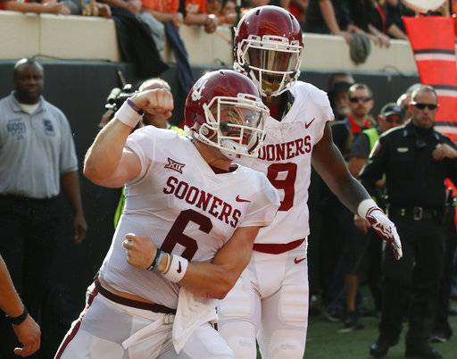 Oklahoma quarterback Baker Mayfield (6) celebrates a touchdown against Oklahoma State in the first half of an NCAA college football game in Stillwater, Okla., Saturday, Nov. 4, 2017. Oklahoma wide receiver CeeDee Lamb is at right.