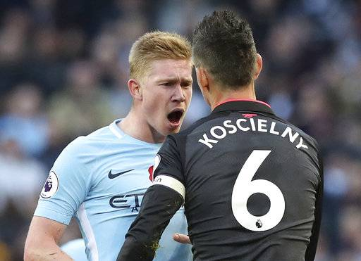 Manchester City's Kevin De Bruyne, left, has words with Arsenal's Laurent Koscielny after a challenge,  during the English Premier League soccer match between Manchester City and Arsenal, at the Etihad Stadium, in Manchester, Sunday, Nov. 5, 2017. (Martin Rickett/PA via AP)