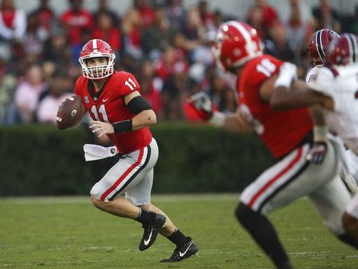 Georgia quarterback Jake Fromm (11) rolls out as he looks for an open receiver during the second half of an NCAA college football game against South Carolina Saturday, Nov. 4, 2017, in Athens, Ga. Georgia won 24-10.