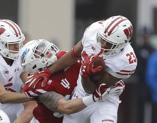 Wisconsin running back Jonathan Taylor (23) runs out of the tackle of Indiana's Chase Dutra (30) during the first half of an NCAA college football game, Nov. 4, 2017, in Bloomington, Ind.