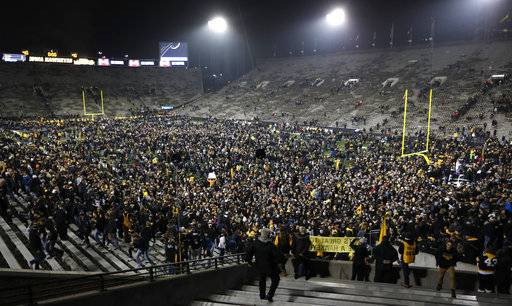 Iowa fans celebrate on the field after an NCAA college football game against Ohio State, Saturday, Nov. 4, 2017, in Iowa City, Iowa.