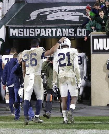 Penn State running back Saquon Barkley (26) and cornerback Amani Oruwariye (21) walk out of Spartan Stadium after an NCAA college football game, Saturday, Nov. 4, 2017, in East Lansing, Mich. Michigan State won 27-24.