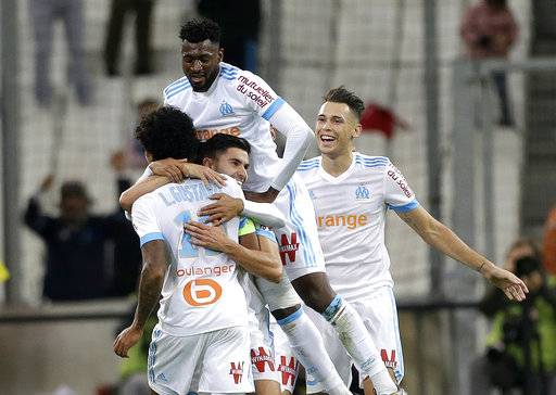 Marseille's players celebrate after Marseille's Luiz Gustavo Dias, back, scored during the League One soccer match between Marseille and Caen, at the Velodrome stadium, in Marseille, southern France, Sunday, Nov. 5, 2017.