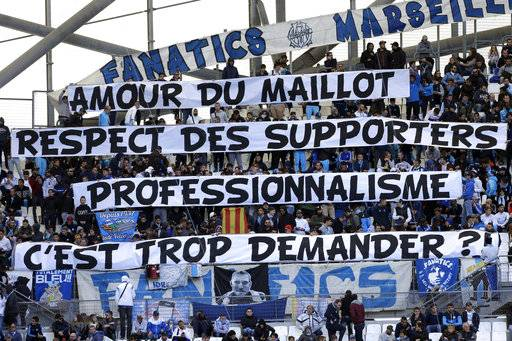 "Marseille supporters display banners reading ""Love of the jersey, respect for supporters, professionalism, is it too much to ask?"", prior to the League One soccer match between Marseille and Caen, at the Velodrome stadium, in Marseille, southern France, Sunday, Nov. 5, 2017. Supporters react after Marseille's player Patrice Evra kicked the head of a supporter of Marseille before the Europa League match against Vitoria SC Guimaraes."