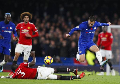 Chelsea's Eden Hazard jumps over Manchester United's Eric Bailly during the English Premier League soccer match between Chelsea and Manchester United at Stamford Bridge stadium in London, Sunday, Nov. 5, 2017.