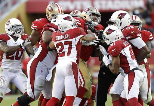 San Francisco 49ers offensive guard Laken Tomlinson, center, shoves Arizona Cardinals players during the second half of an NFL football game in Santa Clara, Calif., Sunday, Nov. 5, 2017.