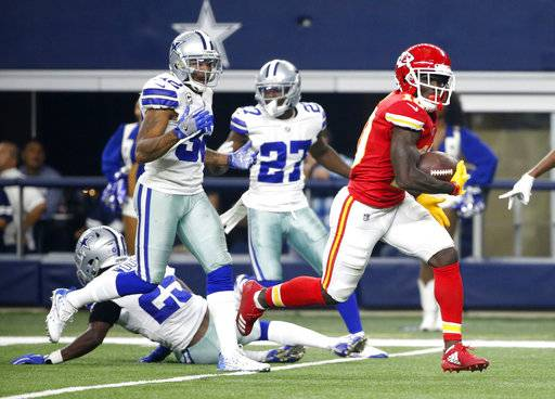 Dallas Cowboys' Xavier Woods (25), Orlando Scandrick (32) and Jourdan Lewis (27) are unable to stop Kansas City Chiefs' Tyreek Hill (10) from reaching the end zone for a touchdown on a long run late in the first half of an NFL football game, Sunday, Nov. 5, 2017, in Arlington, Texas.