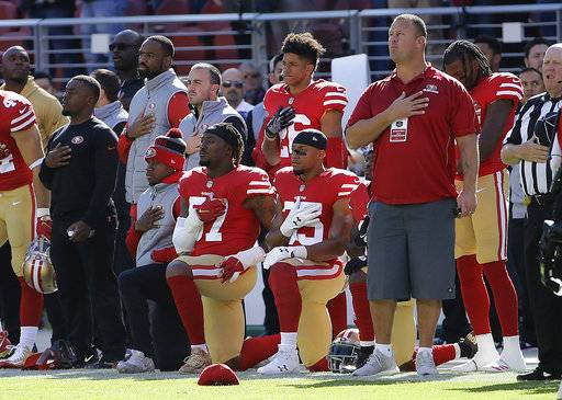 San Francisco 49ers outside linebacker Eli Harold, bottom center, and safety Eric Reid, bottom right, kneel during the national anthem before an NFL football game against the Arizona Cardinals in Santa Clara, Calif., Sunday, Nov. 5, 2017.