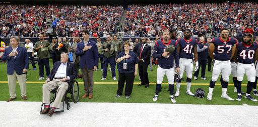 Former President George H.W. Bush, front left, lines up with the Houston Texans for the national anthem before an NFL football game against the Indianapolis Colts, Sunday, Nov. 5, 2017, in Houston.