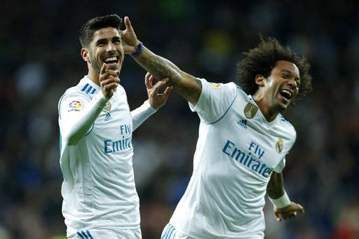 Real Madrid's Marco Asensio, left, celebrates with teammate Marcelo after scoring their side's second goal against Las Palmas during the Spanish La Liga soccer match between Real Madrid and Las Palmas at the Santiago Bernabeu stadium in Madrid, Sunday, Nov. 5, 2017.