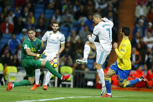 Real Madrid's Cristiano Ronaldo, second right, fails to score past Las Palmas' goalkeeper Raul Lizoain, left, during the Spanish La Liga soccer match between Real Madrid and Las Palmas at the Santiago Bernabeu stadium in Madrid, Sunday, Nov. 5, 2017.