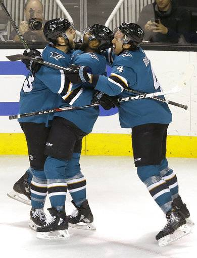 San Jose Sharks right wing Joel Ward, center, is congratulated by right wing Barclay Goodrow, left, and defenseman Brenden Dillon after scoring a goal against the Anaheim Ducks during the third period of an NHL hockey game in San Jose, Calif., Saturday, Nov. 4, 2017. The Sharks won in a shootout, 2-1.