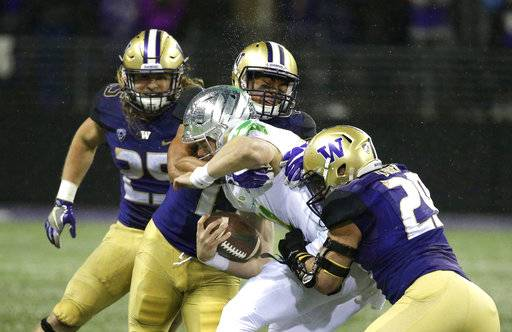 Oregon quarterback Braxton Burmeister is tackled by Washington linebackers Connor O'Brien, right, and Brandon Wellington, upper center, as linebacker Ben Burr-Kirven, left, looks on, in the first half of an NCAA college football game, Saturday, Nov. 4, 2017, in Seattle.