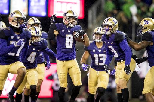 Washington's Dante Pettis celebrates with teammates after his 64-yard punt-return touchdown against Oregon in the first half of an NCAA college football game in Seattle on Saturday, Nov. 4, 2017. Pettis broke the NCAA record for punt returns for touchdowns with nine, after taking a punt back 64 yards for the score in the second quarter on Saturday. (Bettina Hansen/The Seattle Times via AP)