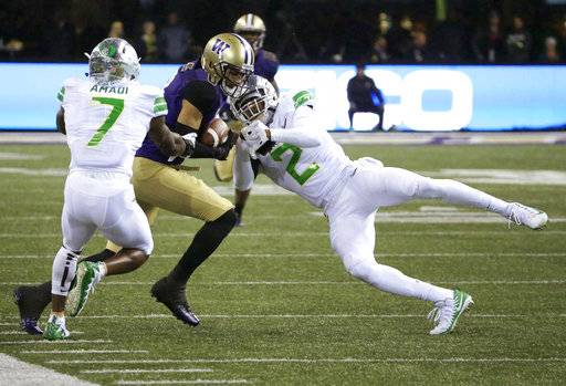 Washington wide receiver Dante Pettis, center, is tackled by Oregon cornerback Ugochukwu Amadi (7) and safety Tyree Robinson (2) after a reception in the first half of an NCAA college football game, Saturday, Nov. 4, 2017, in Seattle.