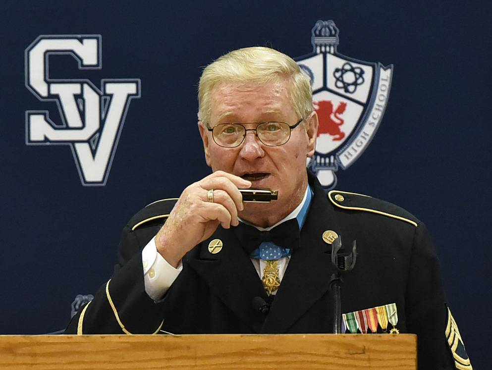 "Retired Army Sgt. Sammy L. Davis performs ""Shenandoah"" on the harmonica while visiting with students Monday at St. Viator High School in Arlington Heights."