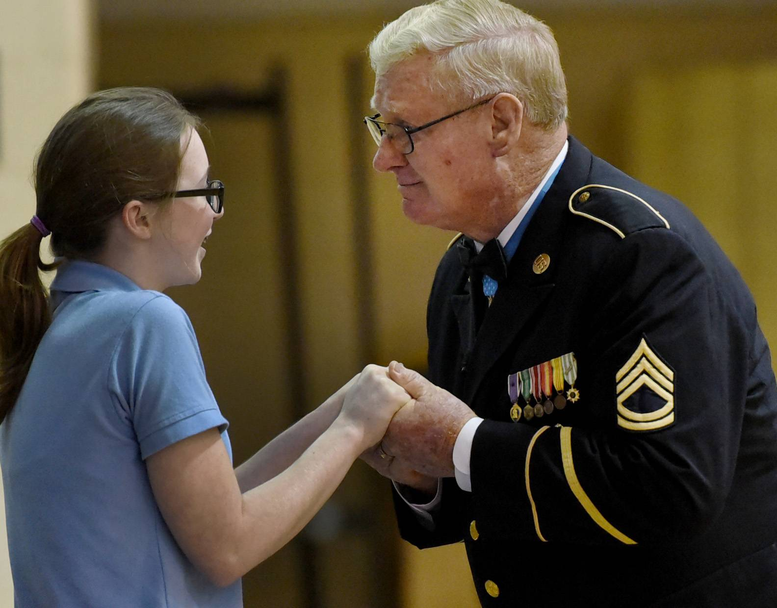 Retired Army Sgt. Sammy L. Davis greets and hugs St. Viator High School sophomore Sarah Conneely after she asked a question Monday during an assembly at the Arlington Heights school.