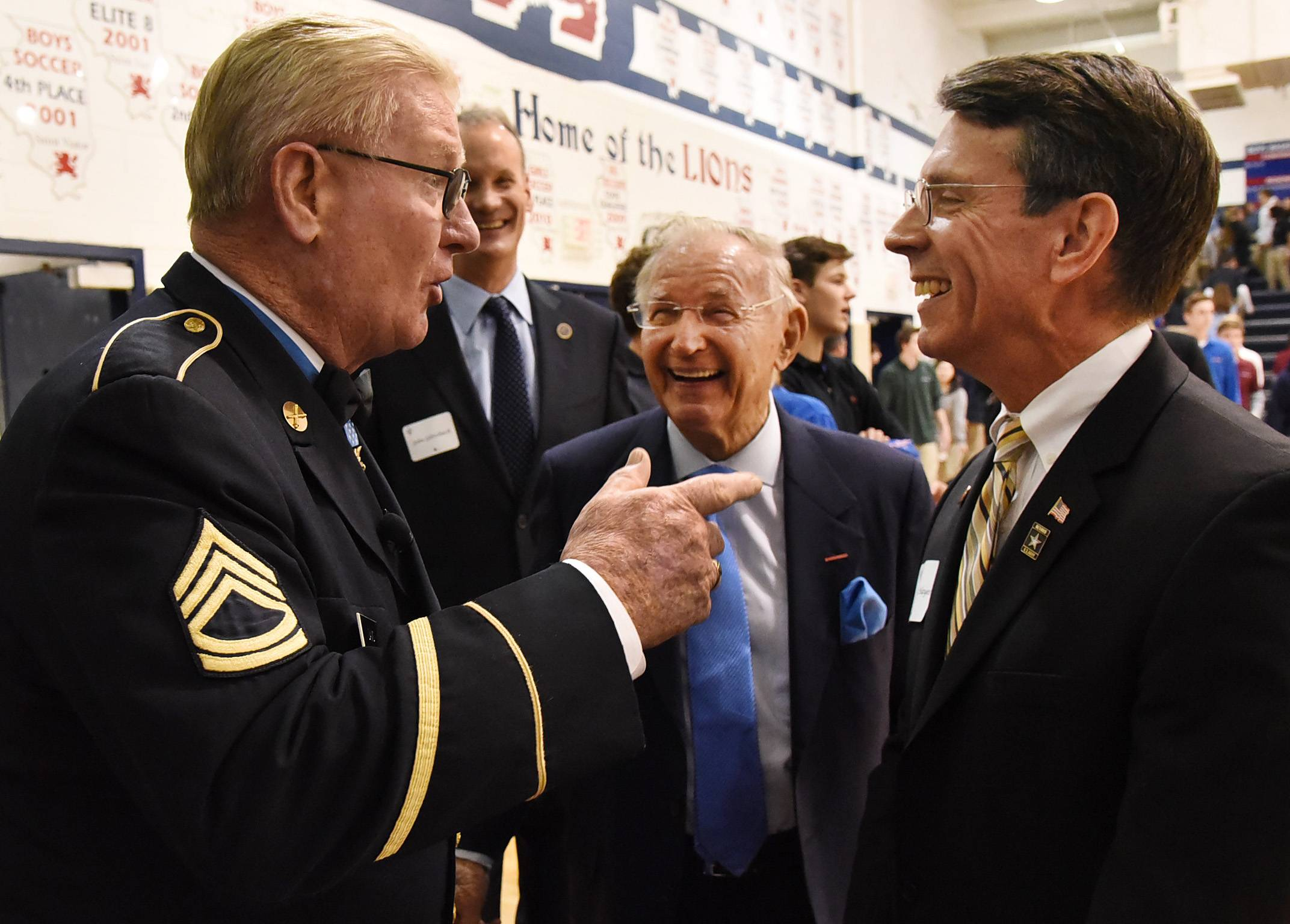 Retired Army Sgt. Sammy L. Davis, speaks with Dick Duchossois and Arlington Heights Mayor Tom Hayes on Monday while visiting St. Viator High School.