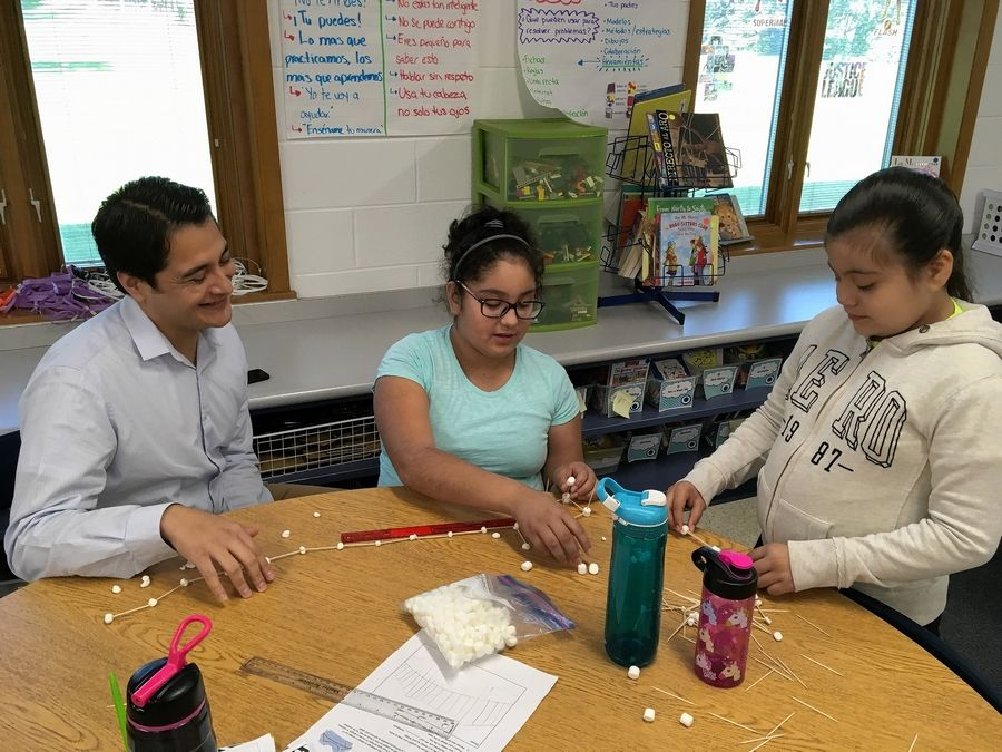 Fourth- and fifth-grade dual language program teacher John Ibarra talks with students about building a bridge for math class.