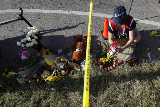 Rebecca Thompson places flowers at a makeshift memorial near the scene of a shooting at the First Baptist Church of Sutherland Springs to honor victims, Monday, Nov. 6, 2017, in Sutherland Springs, Texas. A man opened fire inside the church in the small South Texas community on Sunday, killing and wounding many.
