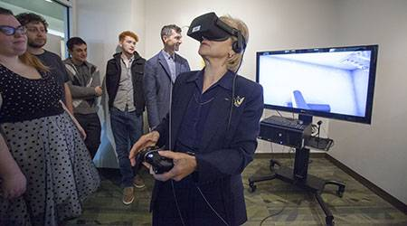 "Pictured: College of DuPage President Dr. Ann Rondeau navigates ""Fracture,"" an interactive 3D game developed by COD students, at the opening reception for the Techcetera Gallery. (Photo by Press Photography Network/Special to College of DuPage)"