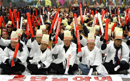 "FILE - In this Nov. 25, 2008, file photo, South Korean farmers shout slogans during an anti-FTA rally near the National Assembly in Seoul, South Korea. The Korean read "" Oppose the FTA between the South Korean and U.S."" President Donald Trump visits South Korea on Tuesday, Nov. 7, 2017, on the second leg of his first official Asian tour. While Trump will be looking to use his trip to strengthen Washington's alliance with Seoul and reaffirm their joint push to maximize pressure on North Korea over its nuclear program, he will also be faced with several thorny issues weighing on the relationship."