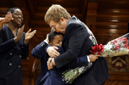 Musician Elton John, right, hugs Chase Sullivan, son of Harvard professors, center left, after Sullivan presented him with flowers during Harvard Humanitarian of the Year Award ceremonies Monday, Nov. 6, 2017, on the campus of Harvard University, in Cambridge, Mass. The musician was presented with the award for his long time work in fighting HIV/AIDS around the world.