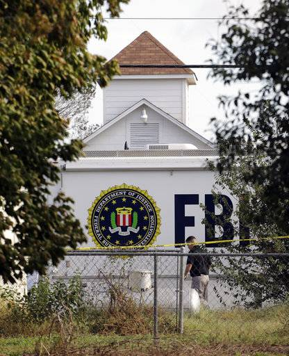 A law enforcement official investigates the scene of a shooting at the First Baptist Church of Sutherland Springs, Monday, Nov. 6, 2017, in Sutherland Springs, Texas. A man opened fire inside the church in the small South Texas community on Sunday, killing and wounding many.