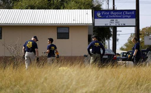 Law enforcement officials investigate the scene of a shooting at the First Baptist Church of Sutherland Springs, Monday, Nov. 6, 2017, in Sutherland Springs, Texas. A man opened fire inside the church in the small South Texas community on Sunday, killing and wounding many.