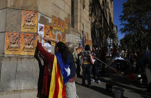 "A woman with an 'Estelada', the pro-independence Catalan flag draped over her shoulder, pastes banners on a wall that read in Catalan: ""Freedom for the Political Prisoners"" during a protest against the decision of a judge to jail ex-members of the Catalan government at the University square in Barcelona, Spain, Sunday, Nov. 5, 2017. A Spanish judge issued an international arrest warrant on Friday for former members of the Catalan Cabinet who were last seen in Brussels, including the ousted separatist leader Carles Puigdemont, who said he was prepared to run for his old job even while battling extradition in Belgium."
