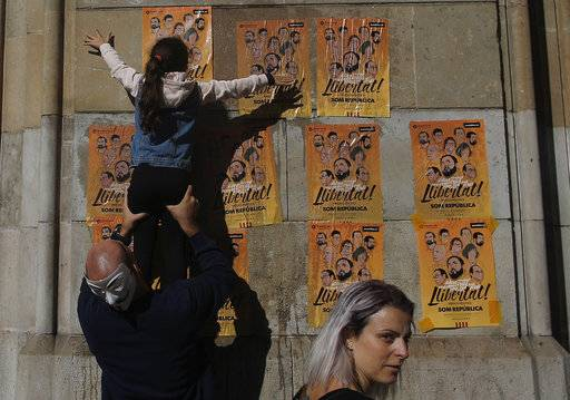 "A girl pastes a banner on a wall that reads in Catalan: ""Freedom for the Political Prisoners"", during a protest against the decision of a judge to jail ex-members of the Catalan government at the University square in Barcelona, Spain, Sunday, Nov. 5, 2017. A Spanish judge issued an international arrest warrant on Friday for former members of the Catalan Cabinet who were last seen in Brussels, including the ousted separatist leader Carles Puigdemont, who said he was prepared to run for his old job even while battling extradition in Belgium."