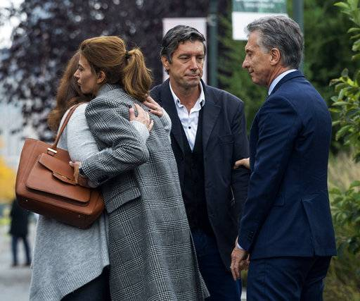 ADDS NAME OF MOURNER AS MARIANA DAGATTI - Mauricio Macri, President of Argentina, right, reaches out to bike attack survivor Guillermo Banchini as Marci's wife Juliana Awada, second from left, embraces Mariana Dagatti, wife of Martin Marro of Argentina who is still hospitalized while officials and others gather for a tribute Monday, Nov. 6, 2017, on the same bike where five citizens from Argentina where struck and killed in a terrorist attack Tuesday, Oct. 31, in New York.