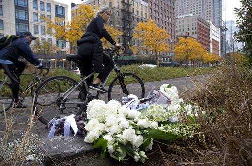 A bicyclist passes bouquets of flowers left by Argentine President Mauricio Macri and New York Mayor Bill de Blasio at the site of the terrorist attack, Monday, Nov. 6, 2017, in New York. Five Argentine bicyclists were among eight people killed by the terrorist who drove a truck down the bike path on Tuesday, Oct. 31.