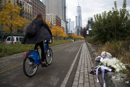 A bicyclist passes bouquets of flowers left by Argentine President Mauricio Macri and New York Mayor Bill de Blasio at the site of the terrorist attack on bicyclists, Monday, Nov. 6, 2017, in New York. Five Argentine bicyclists were among eight people killed by the terrorist who drove a truck down the bike path on Tuesday, Oct. 31.