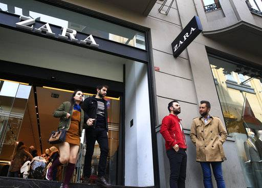 "FILE - In this Friday, Nov. 3, 2017 file photo, people exit and a branch of fashion retailer Zara in an upscale Istanbul neighbourhood. Zara said Monday, Nov. 6, 2017, it is working on establishing a ""hardship fund"" to help a group of Turkish workers who were left unpaid when an outsource factory closed down.The workers went into Zara shops in Istanbul, leaving tags inside garments that read: ""I made this item you are going to buy, but I didn't get paid for it."""