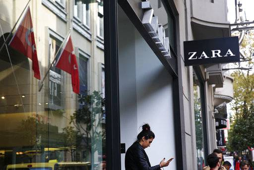 "FILE - In this Friday, Nov. 3, 2017 file photo, a shopper exits a branch of fashion retailer Zara in an upscale Istanbul neighbourhood. Zara said Monday, Nov. 6, 2017, it is working on establishing a ""hardship fund"" to help a group of Turkish workers who were left unpaid when an outsource factory closed down. The workers went into Zara shops in Istanbul, leaving tags inside garments that read: ""I made this item you are going to buy, but I didn't get paid for it."""